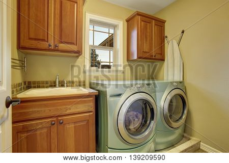 Laundry Room With Washer And Dryer. Wooden Cabinets And Sink
