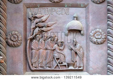 PISA, ITALY - JUNE 06, 2015: Washing of the Feet on the San Ranieri gate of the Cathedral St. Mary of the Assumption in Pisa, Italy on June 06, 2015