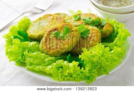 Vegetarian patties of broccoli with salad, pepper, greens and herbs, on white background