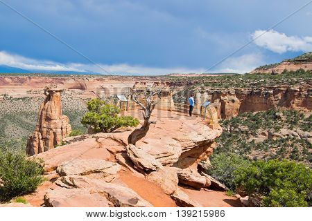A tourist enjoying a spectacular view from Grand View in Colorado National Monument