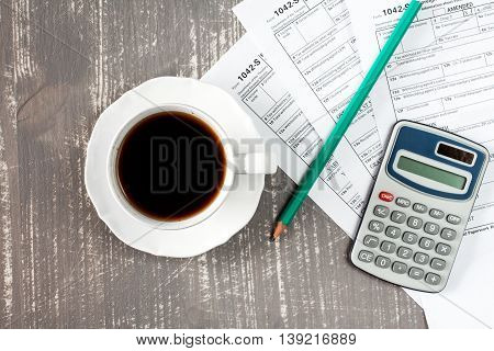 Coffee cup and forms 1042-s which confirms the payment of the tax in the United States
