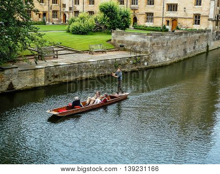 CAMBRIDGE UNITED KINGDOM - JULY 18 2011: Tourists punting in a wooden boat on the river Cam alongside the University of Cambridge historical college buildings.