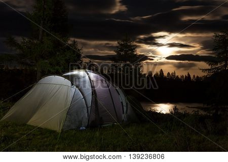Iluminated tent against mountain at moon night