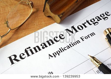 Refinance mortgage form on a wooden table.