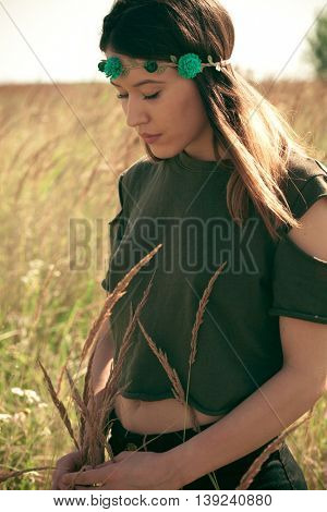 young woman portrait with head band with flowers in summer meadow