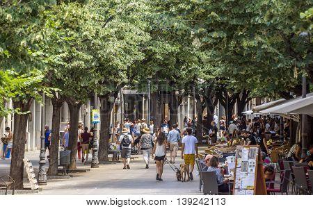 GIRONA SPAIN - JULY 6 2016: Hundreds of people promenading in the busiest street of Girona the Ramblas.