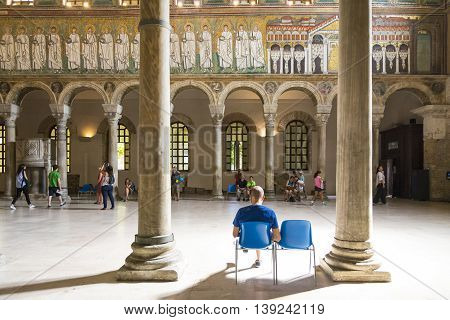 RAVENNA,ITALY-AUGUST 21,2015:people visit the interior of San Appollinare nuovo church in Ravenna-Italyduring a summer day.