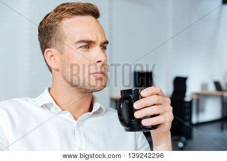 Serious concentrated young businessman drinking coffee in offiice