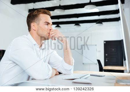 Pensive young businesman working with computer and thinking at workplace