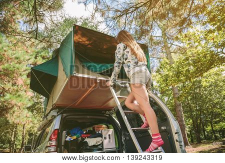 Young woman standing in ladder opening tent door over car. Vacation on the nature concept.