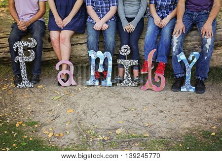 a family sitting on a log in a local park with wooden letters in front of them