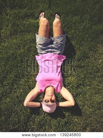 a cute girl laying in green grass on a hot summer day toned with a retro vintage instagram like effect filter app or action