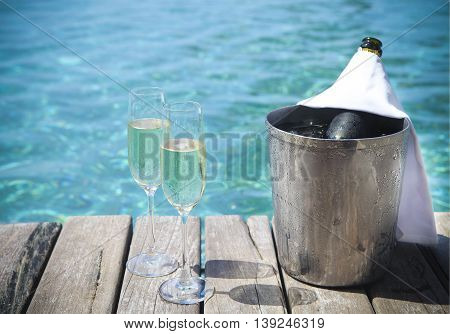Champagne bottle in ice bucket and champagne glasses by swimming pool
