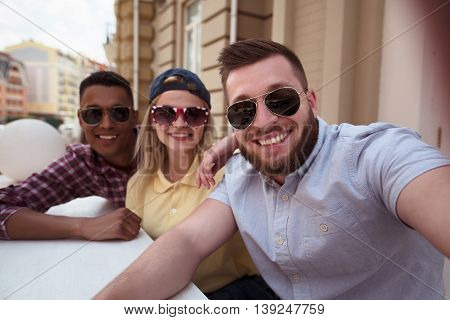 Picture of happy friends posing for camera. Happy peole making selfies on mobile or smart phone outdoors. People spending free time in city centre.