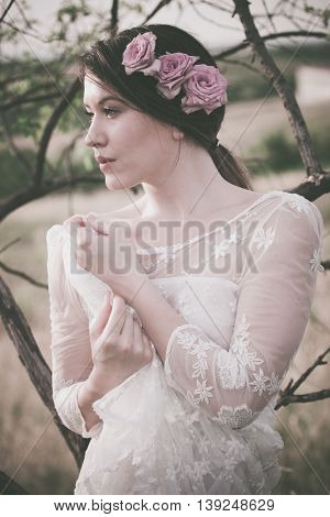 young woman portrait in white lacy dress and roses in hair lean on tree branch summer day