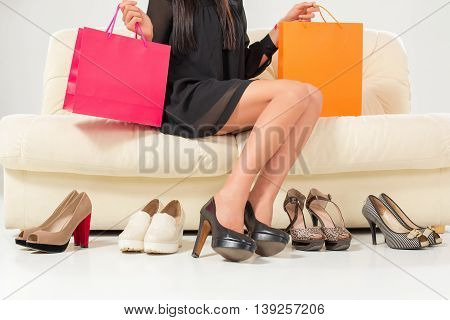 Beautiful legs. Woman trying many shoes. choosing. Sitting on the white sofa. Shopping.