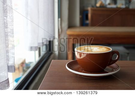 Coffee morning on wood table near window with morning light.