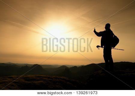 Strong man hiker taking photo with smart phone at mountain peak. Marvelous daybreak.