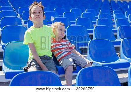 dreary waiting. the two boys took their seats in the stadium and waiting patiently when the game starts or competition