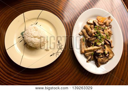 Fried black mushrooms with tofu and rice on the table