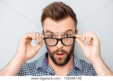 Portrait Of Shocked Modern Man Touching His Spectacles
