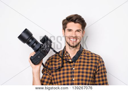 Young Cheerful Photographer Holding Camera  While Working In Studio