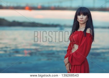 Portrait of a woman in a red dress on the river bank at sunset.