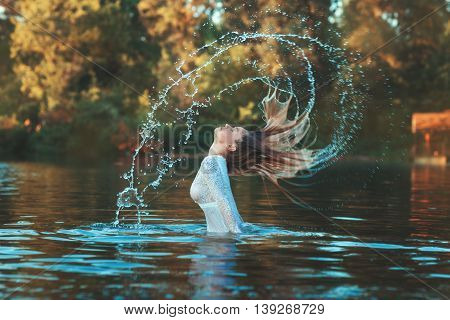 Woman emerged from the water her hair spray droplets she on a lake and forest.