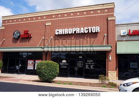 SHOREWOOD, ILLINOIS / UNITED STATES - AUGUST 30, 2015: One may receive chiropractic treatment at Optimal Health & Wellness, and eat pizza at Fat Ricky's restaurant, in a Shorewood strip mall.