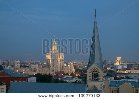 Evangelical Lutheran Church of St. Peter and St. Paul and Stalinist skyscraper on Kotelnicheskaya Quay in night in Moscow