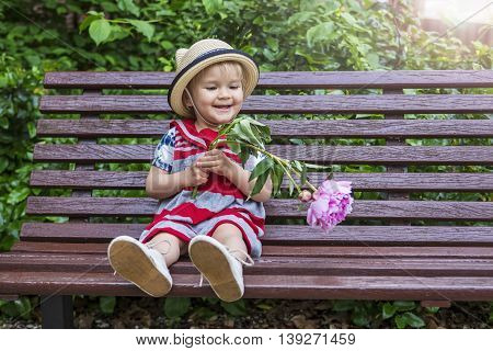 Cute little girl sitting on a bench with a flower