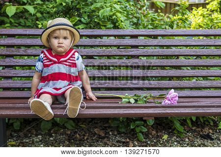 Cute sitting on a bench toddler looking grumpy