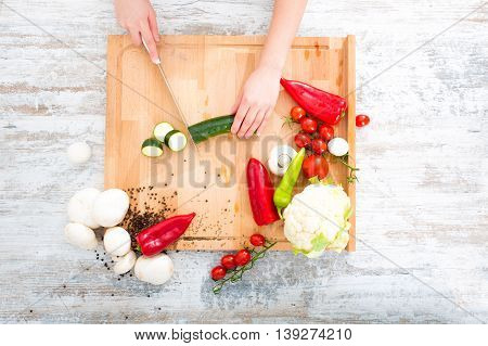 A woman chopping up vegetables at a table.