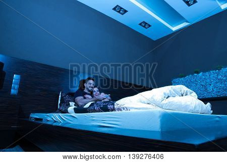 Beautiful young couple watching TV in Bed at night.