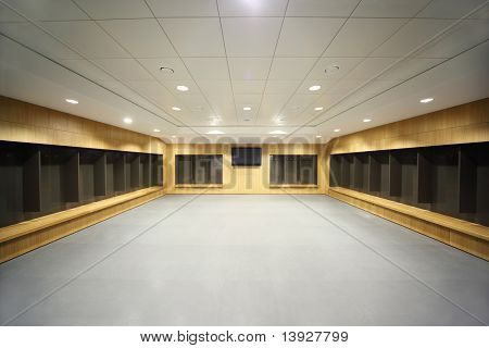 large clean locker room. gray floor and ceiling, big televisor on wall