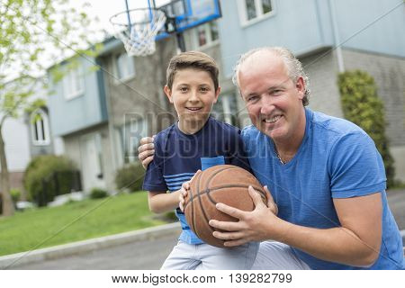 An Image of young man and his son playing basketball