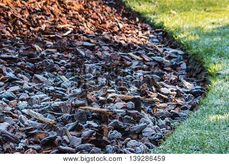 closeup of frost covered wood chips in garden