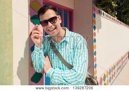 Young stylish confident happy laughing handsome man model in blue t-short in sunglasses. color pattern background