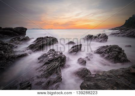Dark of soft waves of ocean in sunset with stones on the beach foreground at Khao Laem Ya Mu Ko Samet National Park Rayong Thailand. Seascape long exposure shot