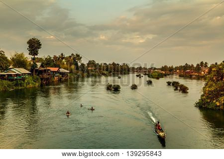 A longboat and swimmers on the Mekong River as the sun sets in Laos