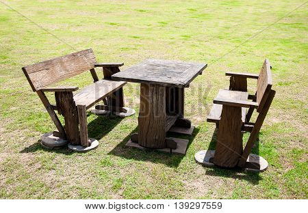 wooden table and chair on green grass yard at noon time