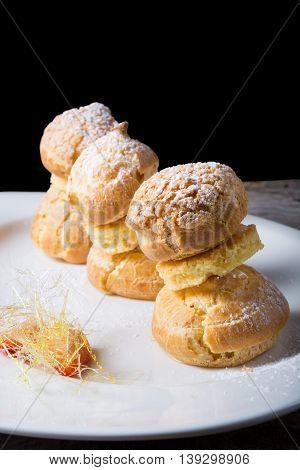 Sweet eclairs dessert served on w hite plate