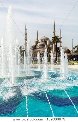 View of the Blue Mosque from the park in Istanbul with a fountain in the foreground. Sultanahmet Camii. Travel Turkey. The Muslim religion.