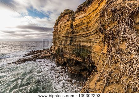 Side of cliff with ocean and cloudy sky at Sunset Cliffs in San Diego, California.