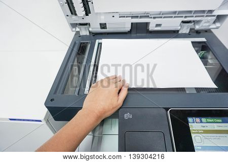 woman scan a document by the printer in the office