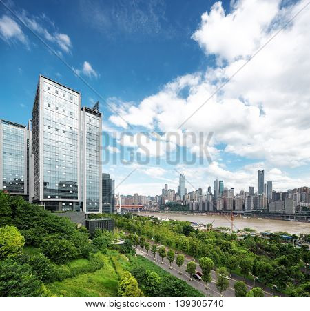 modern office buildings near river in downtown of chongqing in cloud sky