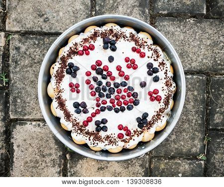 Rounded delicious cake with blueberries and currants in the form. Sweet food theme. International cuisine. Holiday symbol.