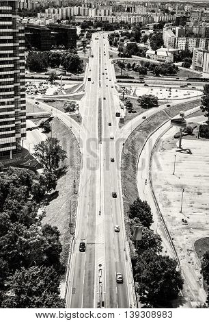Traffic in the city. Urban scene. Straight road and buildings. Bratislava - capital city of Slovakia. Multi-lane road. Black and white photo. Vertical composition.