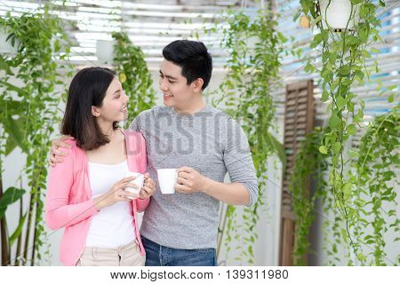 Love couple at home. Young asian relaxing on a balcony's garden.