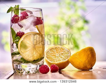 Alcohol cocktail. On wooden boards is glass with alcohol cocktail and ice cubes. Drink number hundred ninety five cocktail raspberry mojito and half lemon with mint. Country life. Outdoor background.